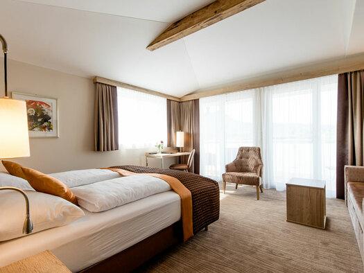 Blick auf das große Fenster, Sessel mit Zierkissen, eine Couch mit Stehlampe davor ein kleiner Tisch, Doppelbett mit Leselampen, kleiner Schreibtisch mit Stuhl. (© Hotel Krone)