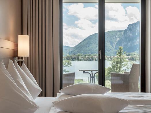 Doppelbett, Lampe, Blick durch die Balkontür auf den Balkon mit Tisch und Stühle, Blick auf den See und die Berge. (© Lackner)