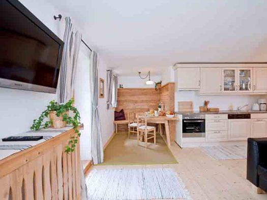 Wohnbereich im Hintergrund der Essbereich mit Tisch und Stühlen, Küche, im Vordergrund eine Couch und Fernseher. (© Gaderer)