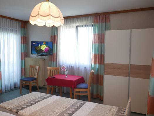 Schlafzimmer mit Doppelbett, Tisch mit Stühlen, Fernseher an der Wand, seitlich und im Hintergrund Balkontür und Fenster, Kleiderschrank. (© Ramsauer)