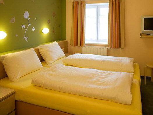 Doppelbett mit Tv an der Wand, Leselampen über dem Bett. (© Oberschmid)