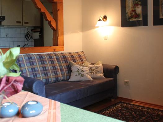 Wohnbereich mit Couch, im Vordergrund Tisch mit Blumen. (© Fam. Winklhofer)