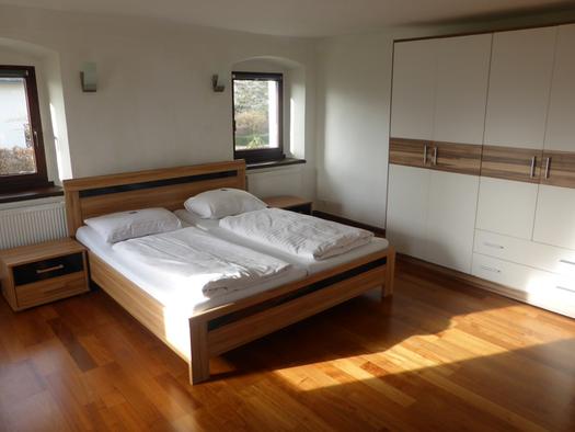 Doppelbett, Nachtkästchen, Fenster, seitlich ein Kleiderschrank. (© Taubenberger)
