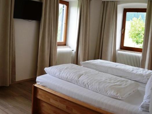 Schlafzimmer mit Doppelbett, im Hintergrund Fenster. (© Pöllmann)