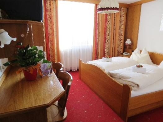 Schlafzimmer mit Doppelbett, im Hintergrund, Fenster, seitlich ein Tisch und Stühle. (© Stabauer)