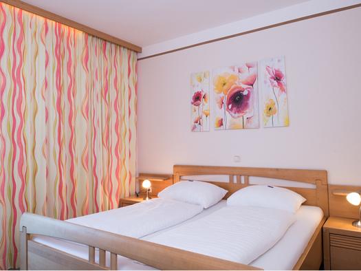 Doppelbett, Nachtkästchen, Tischlampen, im Hintergrund ein Bild ober dem Bett. (© Taubenberger)