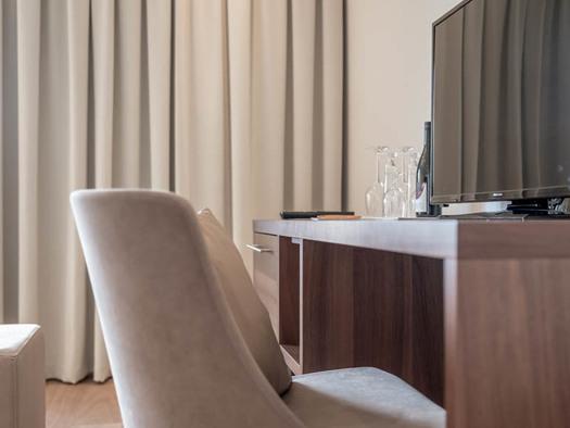 Kommode/Tisch mit Gläser, Flasche, Fernseher, Stuhl. (© Lackner)