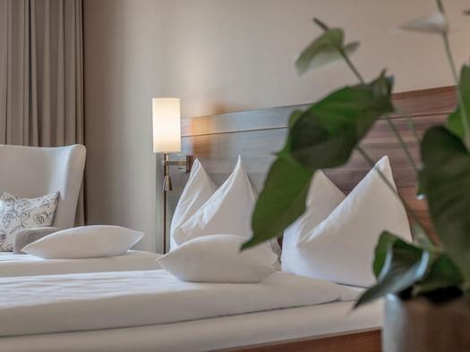 Doppelbett, Lampe, Sessel, im Vordergrund eine Pflanze. (© Lackner)