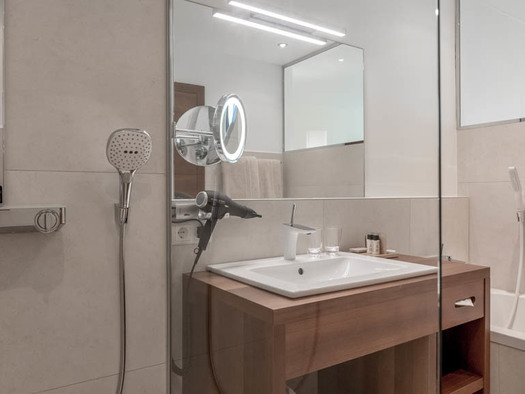 Badezimmer mit Dusche, Waschbecken, Unterschrank, Fön, Spiegel, Badewanne. (© Lackner)
