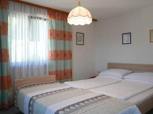 Schlafzimmer mit Doppelbett, davor ein Einzelbett, Nachtkästchen, seitlich ein Fenster. (© Ramsauer)