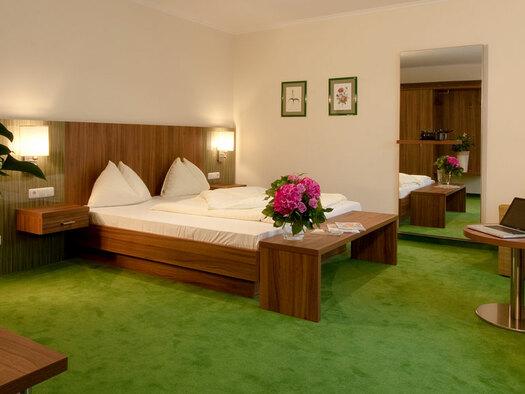 Doppelbett mit Nachtkästchen Lampen darauf, Stühle mit kleinem Tisch großer Spiegel , Bilder an der Wand. (© Hotel Krone)