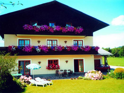 Blick auf das Haus mit Balkon und Blumen, vor den Haus Tisch mit Stühlen, Sonnenschirm, Liegen, Wiese. (© Pichler)