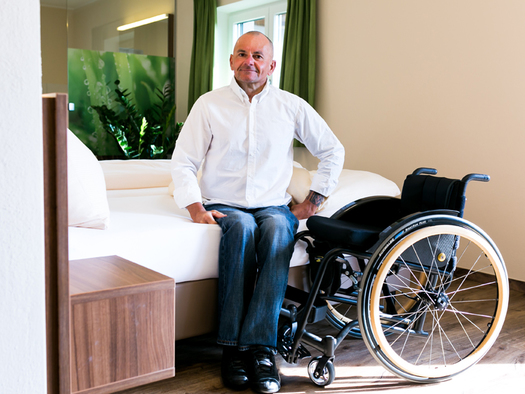 Person sitzt auf dem Bett, daneben Rollstuhl. (© Ellmauer)