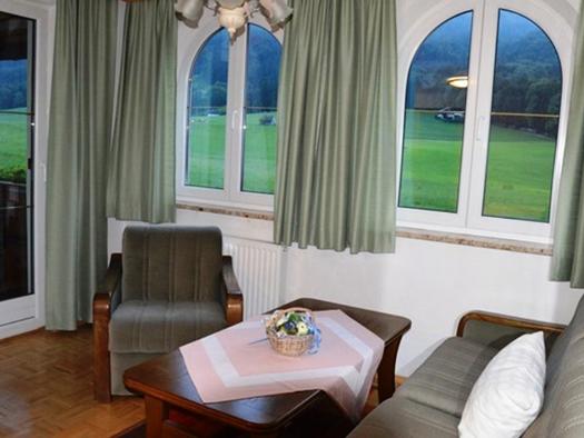 Wohnbereich mit Couch, Tisch und Sessel, im Hintergrund Fenster. (© Pöllmann)