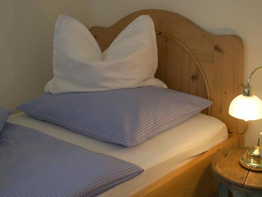 Schlafzimmer mit Bett, Nachtkästchen und Lampe. (© Langwallner)