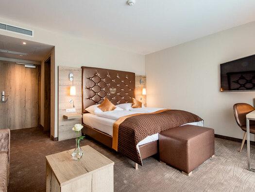 Doppelbett mit Zierkissen, Nachtkästchen mit Lampen, Couch mit kleinem Tisch und Blumenvase, Beistelltisch mit Sessel und Lampe. (© Hotel Krone)