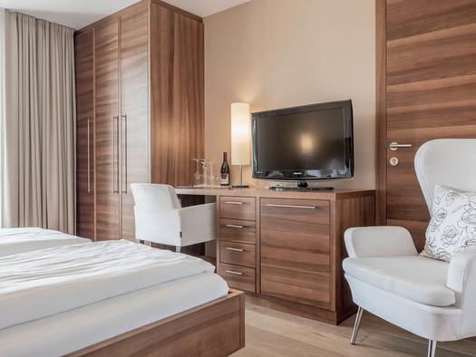 Doppelbett, im Hintergrund ein Kleiderschrank, Tisch/Kommode, Lampe, Fernseher, Stühle. (© Lackner)
