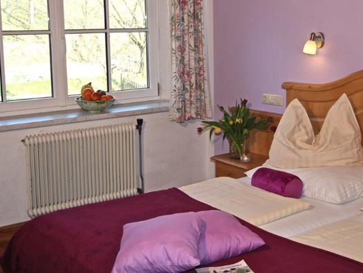 Schlafzimmer mit Doppelbett, seitlich ein großes Fenster. (© Mairhofer)