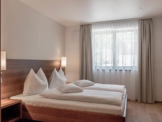 Doppelbett, Lampen, im Hintergrund ein Fenster. (© Lackner)