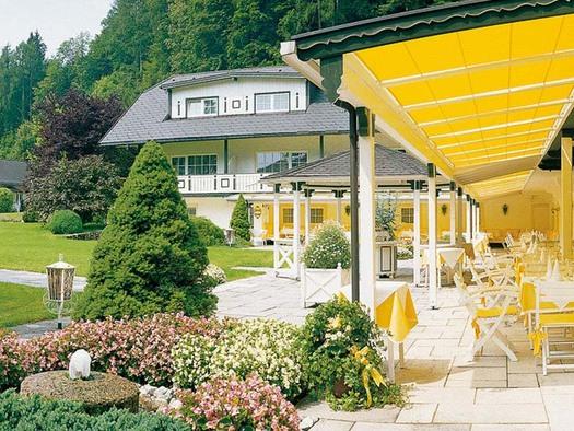 Blick auf die Terrasse mit Tischen und Stühlen unter einer Markise, seitlich Garten mit blühenden Sträucher, Bäume, Haus. (© Hotel Seehof)
