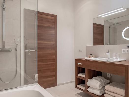 Badezimmer mit Badewanne, Dusche, Bademäntel, Handtücher, Duschtücher in einem Regal, Waschbecken, Spiegel. (© Lackner)
