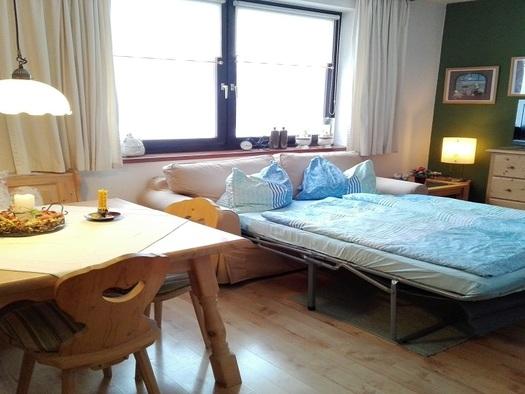 Gemütlicher Wohnraum mit rustikaler Eckbank und Tisch und ausziehbarer Wohncouch. (© Adelheid Haböck)