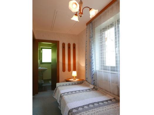 Einzelbett, Nachtkästchen mit Tischlampe, seitlich ein Fenster, Blick durch die offene Tür ins Badezimmer. (© Ramsauer)