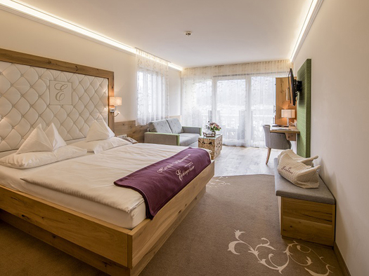 Links das große Vollholzbett, im Hintergrund Couch und Balkontüren auf der rechten Seite Schreibtisch und Flatscreen, Vollholzboden. (© Karin Lohberger)