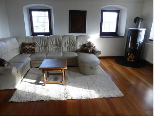 Wohnbereich mit Couch, Tisch, Schwedenofen, im Hintergrund Fenster. (© Taubenberger)