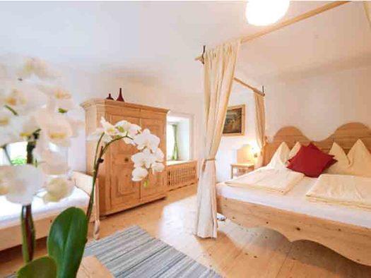 Schlafzimmer mit Himmelbett, im Hintergrund ein Einzelbett, Kasten, Kommode und Fenster, im Vordergrund eine Orchidee. (© Gaderer)