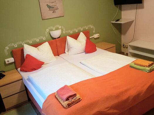Doppelbett mit Zierdecke und Kissen, Nachtkästchen und Bild und TV an der Wand. (© Oberschmid)