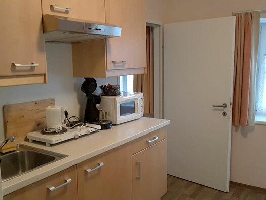 Küchenzeile mit Kochplatten, Mikrowelle und Kaffeemaschine. (© Oberschmid)