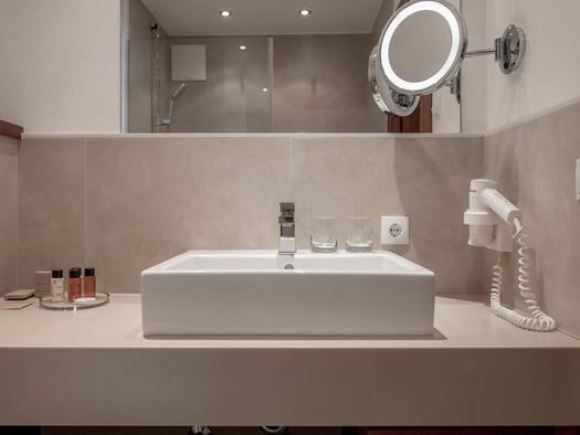 Waschbecken, Fön, Pflegeprodukte in kleine Falschen, Kosmetikspiegel. (© Lackner)