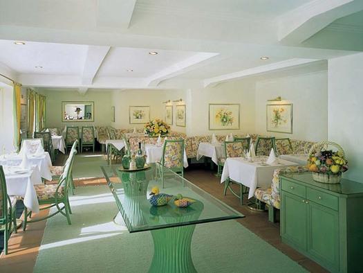 gedeckte Tische mit Stühlen, seitlich eine Kommode mit einem Gesteck, an den Wänden Bilder. (© Hotel Seehof)