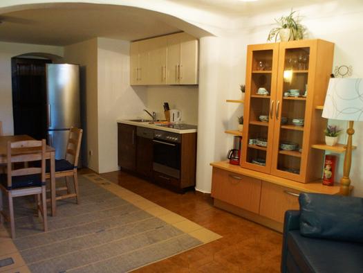 Wohnbereich mit Couch, Stehlampe, Kommode, kleine Kochecke mit Herd, Wasserkocher, Kühlschrank, Tisch und Stühle. (© Taubenberger)