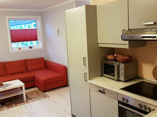 Couch mit kleinem Tisch, Küchenzeile mit Mikrowelle. (© Oberschmid)