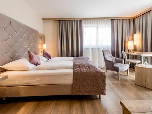 Doppelbett, seitlich Tisch mit Stühle, im Hintergrund Balkontür. (© Hotel Krone)