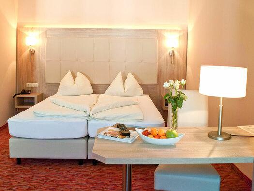 Doppelbett mit Nachtkästchen, Leselampen an der Seite, kleiner Tisch mit Stehlampe, Obstschale und Blumen darauf. (© Hotel Krone)