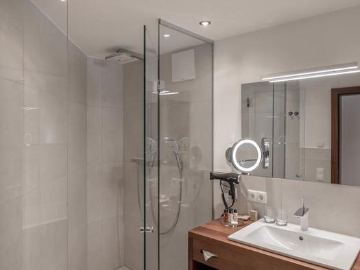 Badezimmer, Dusche, Waschbecken, Fön, Kosmetikartikel in kleine Flaschen, Kosmetikspiegel, Spiegel. (© Lackner)