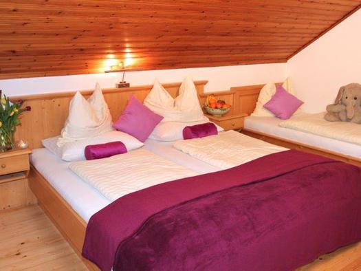 Schlafzimmer mit Doppelbett, Nachtkästchen mit Blumen und Obst, daneben ein Einzelbett mit einem Stofftier. (© Mairhofer)