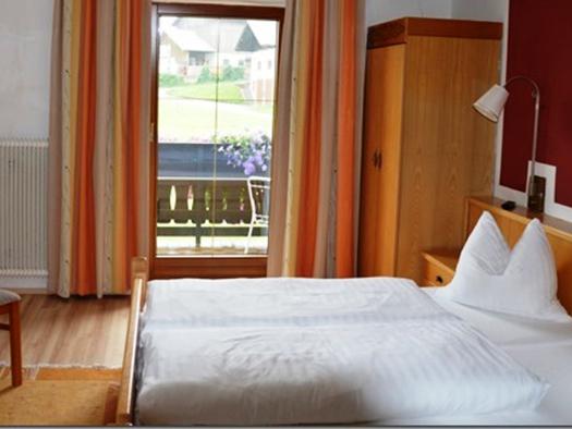 Doppelbett, dahinter ein Schrank, seitlich Tisch mit Stuhl, im Hintergrund befindet sich eine Balkontüre. (© Pöllmann)