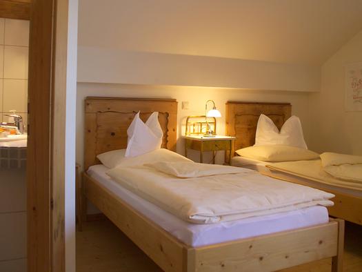 Schlafzimmer mit getrennten Betten, Nachtkästchen mit Lampe, Blick ins Badezimmer auf das Waschbecken. (© Langwallner)