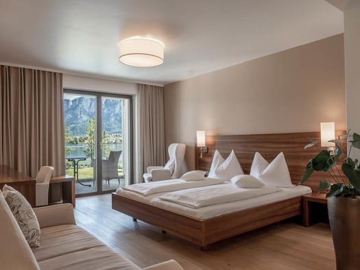 Doppelbett, Stühle, Tisch, Lampen, im Vordergrund großer Topf mit einer Pflanze, seitlich eine Couch, im Hintergrund Blick durch die Balkontür auf die Terrasse mit Stuhl und Tisch, See, Berge. (© Lackner)