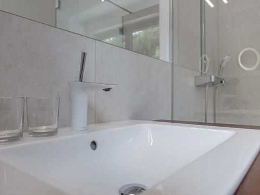 Waschbecken, Gläser, Spiegel, im Hintergrund die Dusche. (© Lackner)