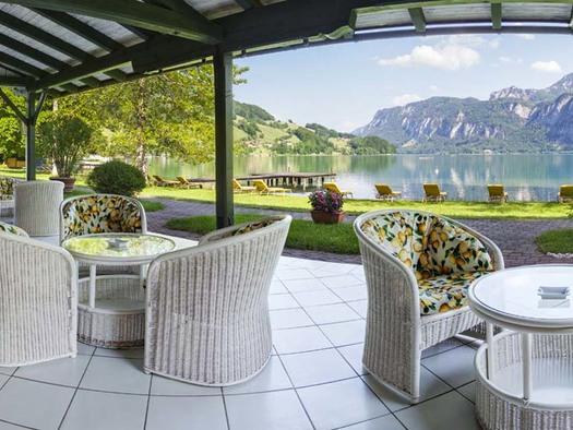 Blick von der Seeterrasse mit Korb-Sesseln, Tische, auf der Wiese Liegestühlen direkt beim See, im Hintergrund die Berge. (© Hotel Seehof)