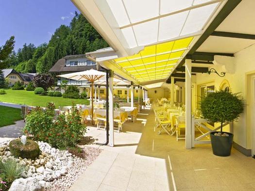 Blick auf die Terrasse mit Stühlen, Tische unter einer Markise und Sonnenschirme, seitlich Steine und Sträucher, Wiesen, Bäume, Häuser. (© Hotel Seehof)