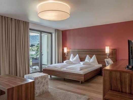 Tisch mit Hocker, Doppelbett, Lampen, seitlich eine Kommode mit einem Fernseher, große Balkontür. (© Lackner)