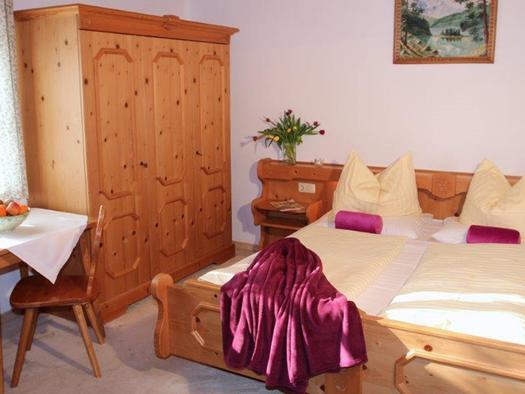 Schlafzimmer mit Doppelbett, seitlich ein Kleiderschrank, im Vordergrund ein Tisch mit Stühle darauf eine Obstschüssel. (© Mairhofer)