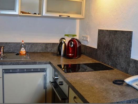 Küche mit Herd, Kaffeemaschine, Wasserkocher, im Vordergrund befindet sich ein Telefon. (© Pöllmann)
