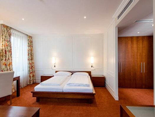 Doppelbett mit Nachttisch und Lampe, langen Vorhängen, kleinem Schreibtisch mit Stuhl, Kleiderschrank. (© Hotel Krone)